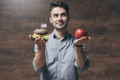 Νεαρός άνδρας που κρατά το κόκκινο μήλο και το εύγευστο χάμπουργκερ Στοκ εικόνες με δικαίωμα ελεύθερης χρήσης
