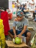 Νεαρός άνδρας που κόβει την καρύδα Στοκ εικόνες με δικαίωμα ελεύθερης χρήσης
