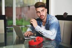 Νεαρός άνδρας που μελετά με την ταμπλέτα, τα ακουστικά και τον καφέ του Στοκ φωτογραφία με δικαίωμα ελεύθερης χρήσης