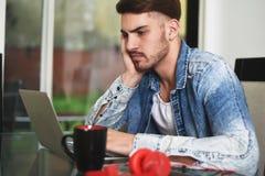 Νεαρός άνδρας που μελετά με την ταμπλέτα, τα ακουστικά και τον καφέ του Στοκ Εικόνα