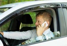 Νεαρός άνδρας που μιλά στο τηλέφωνο πίσω από τη ρόδα ενός αυτοκινήτου Στοκ φωτογραφία με δικαίωμα ελεύθερης χρήσης