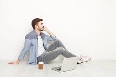 Νεαρός άνδρας που μιλά στο τηλέφωνο στο πάτωμα με το lap-top Στοκ φωτογραφία με δικαίωμα ελεύθερης χρήσης