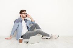 Νεαρός άνδρας που μιλά στο τηλέφωνο στο πάτωμα με το lap-top Στοκ Φωτογραφία