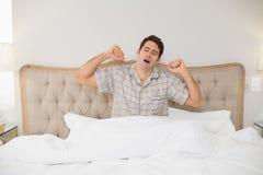 Νεαρός άνδρας που ξυπνά στο κρεβάτι και που τεντώνει τα όπλα του Στοκ Εικόνα