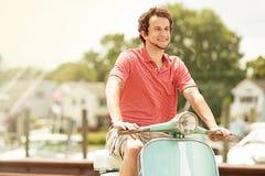 Νεαρός άνδρας που οδηγά το εκλεκτής ποιότητας μηχανικό δίκυκλο στη μαρίνα Στοκ Εικόνα