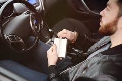 Νεαρός άνδρας που οδηγεί ένα αυτοκίνητο με μια φιάλη σιδήρου Στοκ εικόνες με δικαίωμα ελεύθερης χρήσης