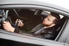 Νεαρός άνδρας που οδηγεί ένα αυτοκίνητο με μια φιάλη σιδήρου Στοκ Εικόνες