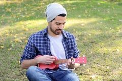 Νεαρός άνδρας που παίζει το ukelele σε ένα πάρκο Στοκ Εικόνες