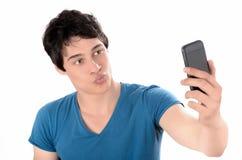 Νεαρός άνδρας που παίρνει μια φωτογραφία φιλήματος selfie με το έξυπνο τηλέφωνό του Στοκ Φωτογραφίες