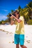 Νεαρός άνδρας που παίρνει τις εικόνες σε μια τροπική παραλία Στοκ Εικόνα