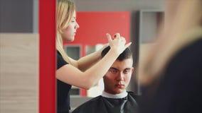 Νεαρός άνδρας που παίρνει το κούρεμα από το θηλυκό κομμωτή καθμένος στην καρέκλα απόθεμα βίντεο