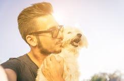 Νεαρός άνδρας που παίρνει selfie με το χαριτωμένο σκυλί του υπαίθριο Στοκ Εικόνα
