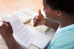 Νεαρός άνδρας που παρουσιάζει ένα έγγραφο με το βαθμό Α συν Στοκ Φωτογραφίες