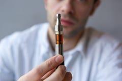 Νεαρός άνδρας που παρουσιάζει ηλεκτρικό τσιγάρο κοντά Στοκ φωτογραφία με δικαίωμα ελεύθερης χρήσης