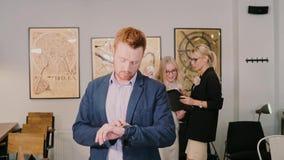 Νεαρός άνδρας που περνά από το σύγχρονο γραφείο και που κοιτάζει στο έξυπνο ρολόι Αρσενική νέα τεχνολογία χρήσεων κίνηση αργή απόθεμα βίντεο