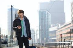 Νεαρός άνδρας που περπατά με την τσάντα και το κινητό τηλέφωνο στην πόλη Στοκ φωτογραφίες με δικαίωμα ελεύθερης χρήσης