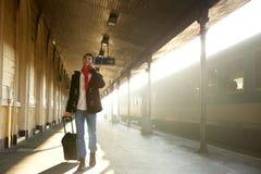 Νεαρός άνδρας που περπατά στο σταθμό τρένου με την τσάντα και το κινητό τηλέφωνο Στοκ Φωτογραφίες