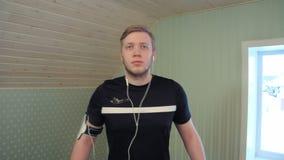 Νεαρός άνδρας που περπατά treadmill και που ακούει τη μουσική απόθεμα βίντεο