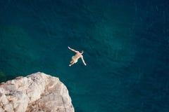 Νεαρός άνδρας που πηδά από τον απότομο βράχο στη θάλασσα στοκ φωτογραφία με δικαίωμα ελεύθερης χρήσης
