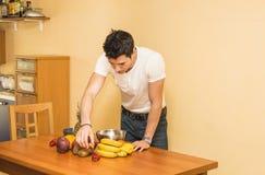 Νεαρός άνδρας που προετοιμάζει μια σαλάτα ή έναν καταφερτζή φρούτων Στοκ εικόνες με δικαίωμα ελεύθερης χρήσης