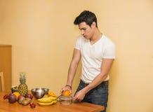 Νεαρός άνδρας που προετοιμάζει μια σαλάτα ή έναν καταφερτζή φρούτων Στοκ εικόνα με δικαίωμα ελεύθερης χρήσης
