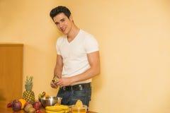 Νεαρός άνδρας που προετοιμάζει μια σαλάτα ή έναν καταφερτζή φρούτων Στοκ φωτογραφία με δικαίωμα ελεύθερης χρήσης