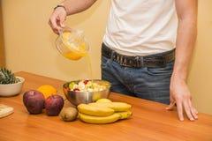 Νεαρός άνδρας που προετοιμάζει μια σαλάτα ή έναν καταφερτζή φρούτων Στοκ Εικόνες