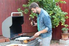 Νεαρός άνδρας που προετοιμάζει το μεσημεριανό γεύμα στη σχάρα Στοκ Εικόνα