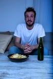 Νεαρός άνδρας που προσέχει τη TV στη νύχτα με τα τσιπ και την μπύρα Στοκ εικόνες με δικαίωμα ελεύθερης χρήσης