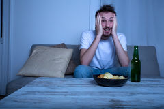 Νεαρός άνδρας που προσέχει τη TV στη νύχτα με τα τσιπ και την μπύρα Στοκ φωτογραφία με δικαίωμα ελεύθερης χρήσης