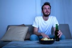 Νεαρός άνδρας που προσέχει τη TV στη νύχτα με τα τσιπ και την μπύρα Στοκ Εικόνες