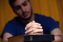 Νεαρός άνδρας που προσεύχεται στην ιερή Βίβλο Στοκ Φωτογραφία