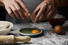 Νεαρός άνδρας που ραγίζει ένα αυγό Στοκ φωτογραφία με δικαίωμα ελεύθερης χρήσης