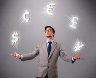 Νεαρός άνδρας που στέκεται και που κάνει ταχυδακτυλουργίες με τα εικονίδια νομίσματος Στοκ Εικόνα