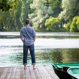 Νεαρός άνδρας που στέκεται στην ξύλινη αποβάθρα, τη χαλάρωση και Στοκ εικόνες με δικαίωμα ελεύθερης χρήσης
