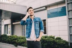 Νεαρός άνδρας που στέκεται υπαίθρια, που μιλά στο τηλέφωνο στοκ εικόνα