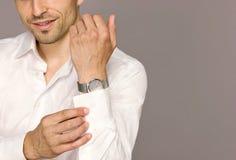Νεαρός άνδρας, που στερεώνεται σε ένα άσπρο πουκάμισο Στοκ Φωτογραφίες