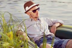 Νεαρός άνδρας που στηρίζεται στη βάρκα Στοκ Φωτογραφίες