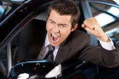 0 νεαρός άνδρας που σφίγγει την πυγμή του, καθμένος στο νέο αυτοκίνητο και την κραυγή Στοκ Φωτογραφία