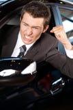 0 νεαρός άνδρας που σφίγγει την πυγμή του, που κάθεται στο νέο αυτοκίνητο Στοκ Φωτογραφίες