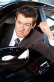 0 νεαρός άνδρας που σφίγγει την πυγμή του, που κάθεται στο νέο αυτοκίνητο Στοκ Εικόνες