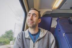 Νεαρός άνδρας που ταξιδεύει σε ένα τραίνο και τα βλέμματα έξω το παράθυρο και smil Στοκ εικόνα με δικαίωμα ελεύθερης χρήσης