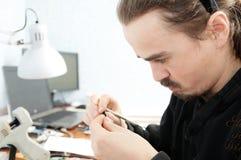 Νεαρός άνδρας που το χειροποίητο μικροσκοπικό πλαστικό παιχνίδι, χόμπι χειροτεχνίας διακοσμήσεων σπιτιών, διαδικασία δημιουργιών Στοκ φωτογραφία με δικαίωμα ελεύθερης χρήσης