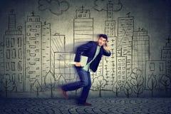 Νεαρός άνδρας που τρέχει αργά στην εργασία που μιλά στο κινητό τηλέφωνο Στοκ φωτογραφίες με δικαίωμα ελεύθερης χρήσης