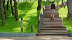 Νεαρός άνδρας που τρέχει επάνω σε σε αργή κίνηση Να δημιουργήσει νεαρών άνδρων σκαλοπάτια στο πάρκο απόθεμα βίντεο