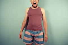 Νεαρός άνδρας που τραβά τα ανόητα πρόσωπα Στοκ φωτογραφίες με δικαίωμα ελεύθερης χρήσης