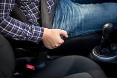 Νεαρός άνδρας που τραβά handbrake το μοχλό στο αυτοκίνητο στοκ φωτογραφίες