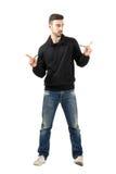 Νεαρός άνδρας που τραβά hoodie τις δαντέλλες που κοιτάζουν μακριά Στοκ Εικόνες