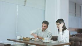 Νεαρός άνδρας που τρώει ενώ η φίλη του που μιλά στο τηλέφωνο στο εστιατόριο απόθεμα βίντεο