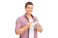 Νεαρός άνδρας που τρώει τα σούσια με τα κινεζικά ραβδιά Στοκ Φωτογραφίες